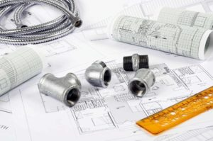 plumbing fittings on top of paper plans